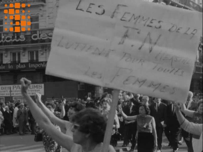Archives Sonuma, Bulletin d'actualité, 1 mai 1966. Défilé du 1er mai 1966 à Bruxelles. Charlotte Hauglustaine fait ici figure de fer de lance du mouvement : le poing levé, tenant un calicot « les femmes de la FN Herstal luttent pour toutes les femmes », elle chante « Le travail, c'est la santé… ». Le montage du sujet d'actualité fait précéder et suivre ce portrait d'images de femmes qui, dans un champ-contrechamp, apparaissent comme les destinataires du geste et du chant de l'ouvrière de la FN. Cette séquence donne ainsi une certaine envergure au mouvement de contestation tout en le circonscrivant à des cercles féminins.